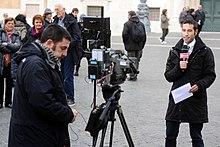 Un giornalista televisivo e il suo cameraman durante un collegamento in esterna