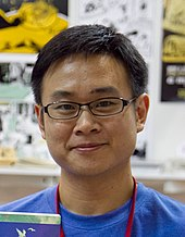 A bespectacled man wearing a blue T-shirt