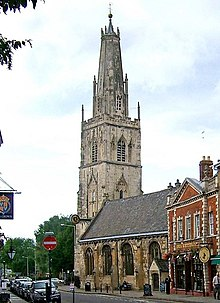 A stone church in a town seen from the southeast. St the far end is a large tower surmounted by a truncated spire with pinnacles and, at the top, a ball finial