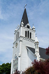 A white church steeple, with a black pointed roof.
