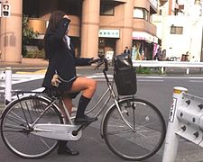 Stereotypical Japanese school girl in Japan on a bike - 2014.jpg