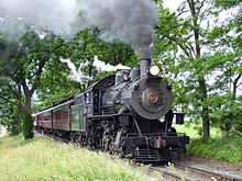 Steam engine pulling passenger cars through a wooded area
