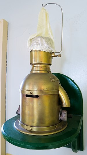 "Chance Brothers - A 85mm Chance Brothers Incandescent Petroleum Vapour Installation which produced the light for the Sumburgh Head lighthouse until 1976. The lamp (made in approx. 1914) burned vaporized kerosene (paraffin); the vaporizer was heated by a denatured alcohol (methylated spirit) burner to light. When lit some of the vaporised fuel was diverted to a Bunsen burner to keep the vaporizer warm and the fuel in vapor form. The fuel was forced up to the lamp by air; the keepers had to pump the air container up every hour or so. This in turn pressurized the paraffin container to force the fuel to the lamp. The ""white sock"" is in fact an unburnt mantle on which the vapor burned."