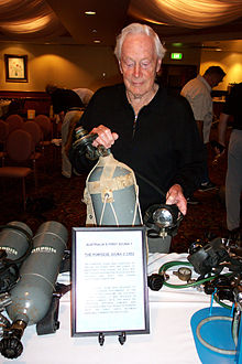 "Eldred is holding a grey scuba cylinder and regulator with a sign titled ""Australia's first scuba? The Porpoise scuba c 1953""."