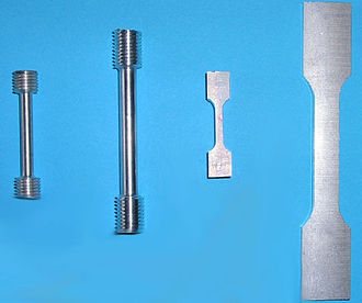 Tensile testing - Tensile specimens made from an aluminum alloy. The left two specimens have a round cross-section and threaded shoulders. The right two are flat specimens designed to be used with serrated grips.