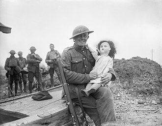 "Tommy Atkins - A publicity photograph of ""Tommy Atkins"", a soldier of the 51st Division, seated with a large doll in his arms, taken during the German offensive in Lys, 13 April 1918"