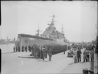 HMS Birmingham (C19) - Field Marshal Montgomery saluting from his car while passing down a quayside lined with a Royal Marine Guard of honour from Birmingham. The Field Marshal had just landed at Copenhagen, Denmark following its liberation by British forces. Birmingham is moored to the quayside and her crew line the decks