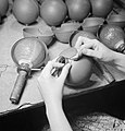 The protective casing being clipped into place around the glass flask of a No.74 Grenade, known as a 'sticky bomb' at a workshop in Britain during 1943. D14772.jpg