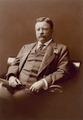 Theodore Roosevelt, three quarter-length portrait, seated left, facing forward, wearing flower in lapel.tif