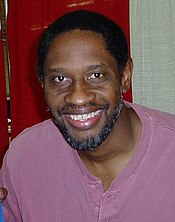 A dark-skinned man with black hear and a greying beard and moustache is wearing a violet shirt and smiling into the camera.