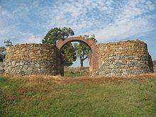Photographie en couleur d'un monument en ruines, deux tours et une porte apparaissent