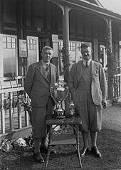 Two gentlemen golfers outside Llandrindod Wells Golf Club pavilion, with two cups