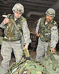 U.S. Air Force Tech. Sgt. Ross Richard, left, and Senior Airman Jose Rodriguez grab their mobility bags while processing through a deployment line at the Joint Mobility Center on Eielson Air Force Base.jpg