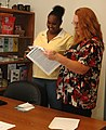 US Army 50776 Sharon Bass, spouse of Sgt. Bass, 15th SB receives information from Julie Grant, Family readiness support assistant 15th STB at the grand opening of the 15th SB Soldier and Family readiness center at.jpg