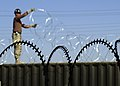 US Navy 040324-N-1261P-017 Builder 2nd Class Ferdy Ramirez assigned to Naval Mobile Construction Battalion Seventy Four (NMCB-74) stretches a spool of concertina wire around the Seabees main compound.jpg