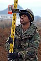 US Navy 050215-N-2385R-023 Engineering Aide Constructionman Doug Gaffney, assigned to Naval Mobile Construction Battalion Four Zero (NMCB-40), Detachment Sasebo, uses a Philadelphia Rod to adjust for elevation.jpg