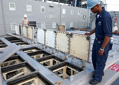 US Navy 050714-N-0874H-001 Gunner's Mate 2nd Class Charles Coleman inspects missile cell hatches on one of two Vertical Launching Systems (VLS) aboard the guided missile cruiser USS Hue City (CG 66).jpg