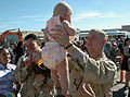 US Navy 070301-N-7365L-011 A Sailor assigned to Naval Mobile Construction Battalion (NMCB) 5, embraces his baby for the first time during a homecoming ceremony for the Seabees.jpg
