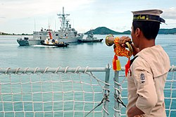 US Navy 070618-N-7783B-004 A crew member of the Royal Thai Navy Ship HTMS Similan (187) renders a bugle salute to the guided missile frigate USS Jarrett (FFG 33).jpg