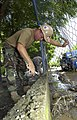 US Navy 090704-F-7923S-211 Equipment Operator 3rd Class Kevin Funk, assigned to Construction Battalion Maintenance Unit (CBMU) 202, cuts out an existing chain link fence.jpg