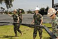 US Navy 100414-N-0318S-032 Seabees from Naval Mobile Construction Battalion (NMCB) 3, Headquarters Company, position the frame of a modular general purpose tent system.jpg