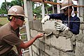 US Navy 110701-N-WL717-140 Builder 2nd Class Daniel Allen scrapes mortar as a Philippine navy Seabee embeds the brick for the wall of a new school.jpg