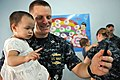 US Navy 111025-N-WW409-387 Lt. John Lundgren, assigned to the guided-missile destroyer USS Mustin (DDG 89), plays with a child at the Pattaya Orpha.jpg
