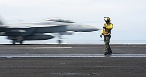 US Navy 120123-N-OY799-139 Aviation Boatswain's Mate (Handling) 2nd Class Roberto Andiarena checks the time as an F-A-18F Super Hornet from the Bla.jpg