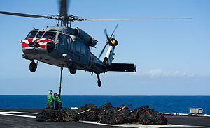 US Navy 120212-N-OY799-517 Logistics Specialist Seamen Cody James and Rachel Foster hook cargo to an MH-60S Sea Hawk helicopter from the Eightballe.jpg