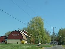 "A red and beige barn with the words ""Unionville Vineyards"" with the intersection of 2 gravel roads in the foreground."
