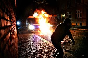Molotov Cocktail. at a police van.  Protester throwing.
