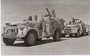 vehicles in convoy, each crewed by three men, in a desert terrain