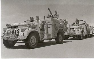 "Long Range Desert Group - LRDG Headquarters Section (note markings on ""Louise"") of Chevrolet 30 cwt. The first two vehicles are armed with Vickers guns, and have canvas sand mats rolled up and stored on the front wheel arches."