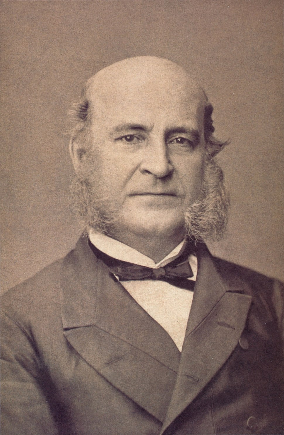 Photograph showing the head and shoulders of an older man with large sideburns and wearing a formal coat and black bow tie
