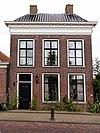 foto van Pand met verdieping onder dwars schilddak met twee hoekschoortenen en voorbouw met zesruitsvensters en versierde kroonlijst