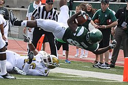 A player diving with his back to the ground as he crosses into the end zone