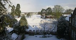A panoramic vista of school playing fields covered in snow. Two large trees are visible to the left, schoolrooms to the right. A number of pupils are seen playing in the snow.