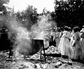 Women standing near large cooking cauldron and pile of oyster shells, June 25, 1898 (WASTATE 2556).jpeg