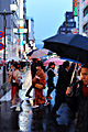 Young japanese women wearing traditional outfit crossing crounded street of downtown Kyoto.jpg