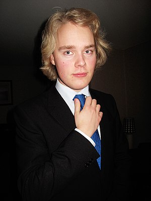 English: A young man wearing a suit at New Years.