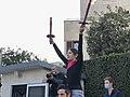 המפגינה נאוה רוזוליו מניפה 2 לפידים מול הווילון השחור של בית ראש הממשלה בשבת אחר הצהריים 26בדצמבר 2020.jpg
