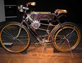 A pristine-looking, spindly turn-of-the-century style motorcycle with a chain and pedals like a bicycle, and a flame lantern for a headlight.  A leather belt delivers power from the engine to the rear wheel.