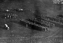 A large number of people standing in formation in a field. Two biplanes are visible at the upper left, with a smaller group of people standing in front of them.