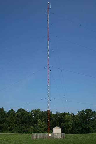 "Mast radiator - A typical mast radiator and ""helix house"" of an AM radio station in Chapel Hill, North Carolina. The high RF voltage on the mast can deliver a dangerous electrical shock to anyone touching it, so the base is surrounded by a fence to prevent access."