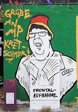 """Graffiti in der Alaunstraße in Dresden. Das Motiv bezieht sich auf die Auseinandersetzung während einer Pegida-Demonstration zwischen einem Kamerateam von Frontal 21 und einem Demonstrationsteilnehmer sowie die umstrittene Polizeiaktion, welche die Pressearbeit behinderte. """"Grüße an MP Kretschmer"""" – """"Frontal-Aufnahme, LKA"""""""