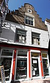 foto van Huis met gedeeltelijk gecementeerde trapgevel. De treden afgedekt met natuurstenen platen. Moderne winkelpui