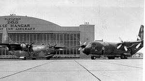 Westover Air Reserve Base -  A C-123K Provider (731st Tactical Airlift Squadron) and a C-130B Hercules (337th Tactical Airlift Squadron) are in front of the Westover Air Force Base Hangar for a 1977 publicity photo.