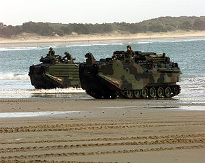 Two U.S. Marine Corps Amphibious Assault Vehicles emerge from the surf onto the sand.