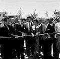 Adolfo López Mateos y Virginia Soto Rodríguez acompañados de funcionarios públicos en el momento de cortar un listón en una inauguración.jpg