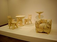 Four cafe chairs and a table, a high table, and an upholstered chair are wrapped in fabric and rope.